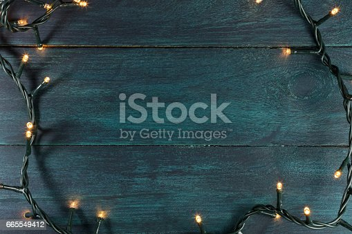 istock Fairy lights on a dark wooden texture, holiday background 665549412