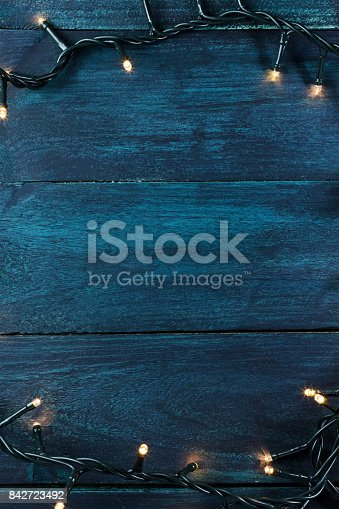 istock Fairy lights on a dark wooden texture, holiday background 842723492