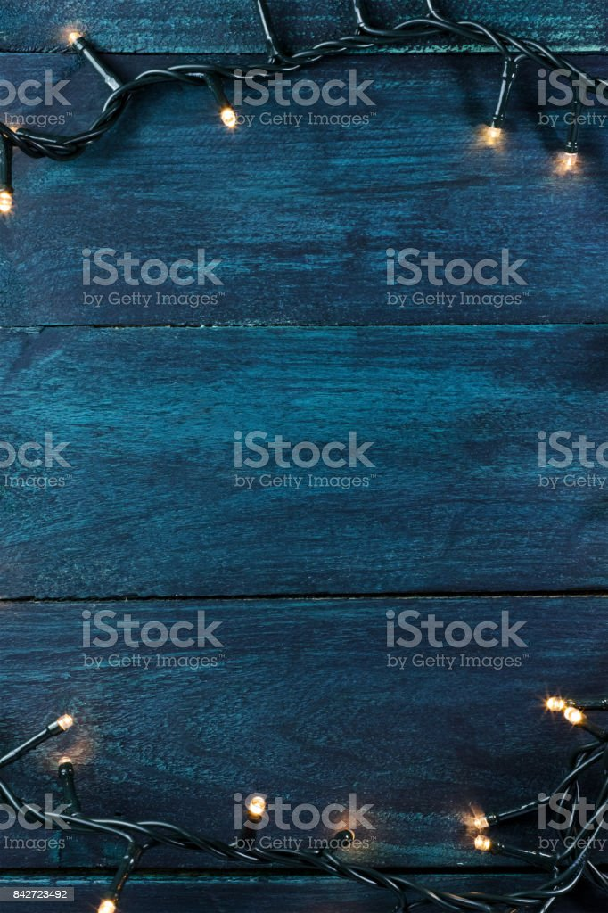 Fairy lights on a dark wooden texture, holiday background stock photo