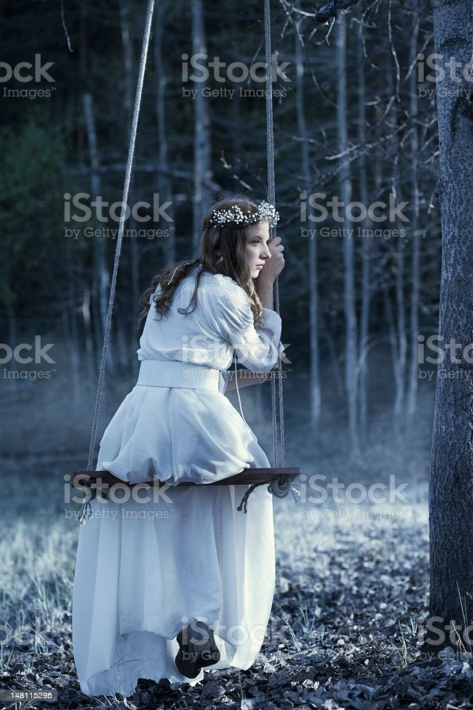 Fairy on swing in night forest royalty-free stock photo