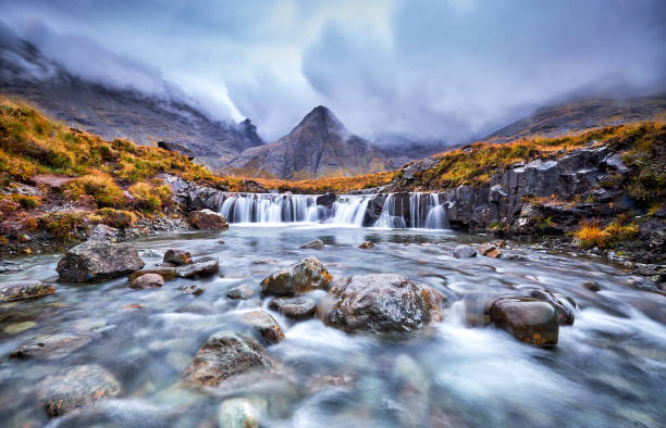 Fairy Pools, Glen Brittle, Isle of Skye, Scotland, UK Waterfall in the Fairy Pools, Glen Brittle, Isle of Skye, Scotland, UK. On a gray day in the fall you see the water flowing along the rocks with in the background the famous mountain with the crack in the middle from top to bottom scottish highlands stock pictures, royalty-free photos & images