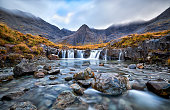 Waterfall in the Fairy Pools, Glen Brittle, Isle of Skye, Scotland, UK. On a gray day in the fall you see the water flowing along the rocks with in the background the famous mountain with the crack in the middle from top to bottom