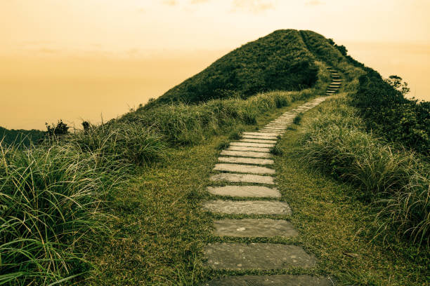 Fairy tale landscape and stepping stone path over a hill on the horizon at the Caoling Historic Trail in Taiwan stock photo