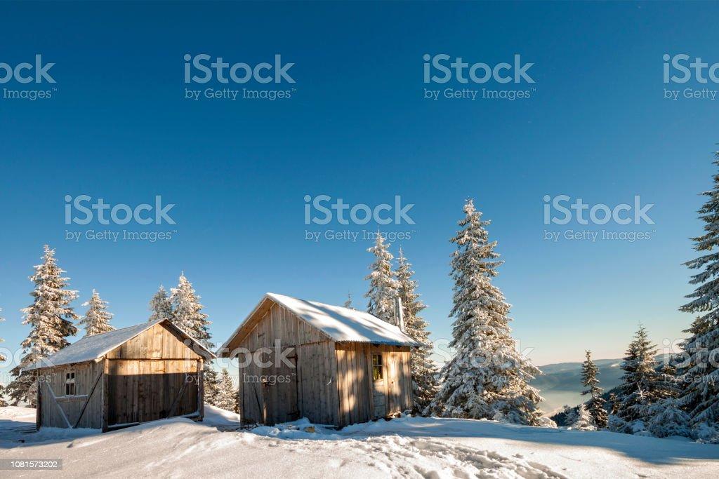 Fairy tale winter sunny landscape. Two weathered wooden shepherd huts...