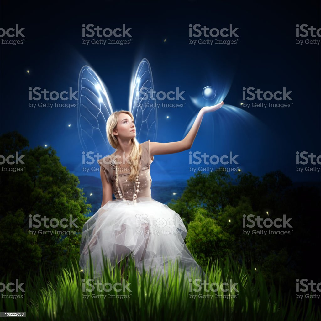 Fairy Woman Holding Orb and Sitting in Grass stock photo