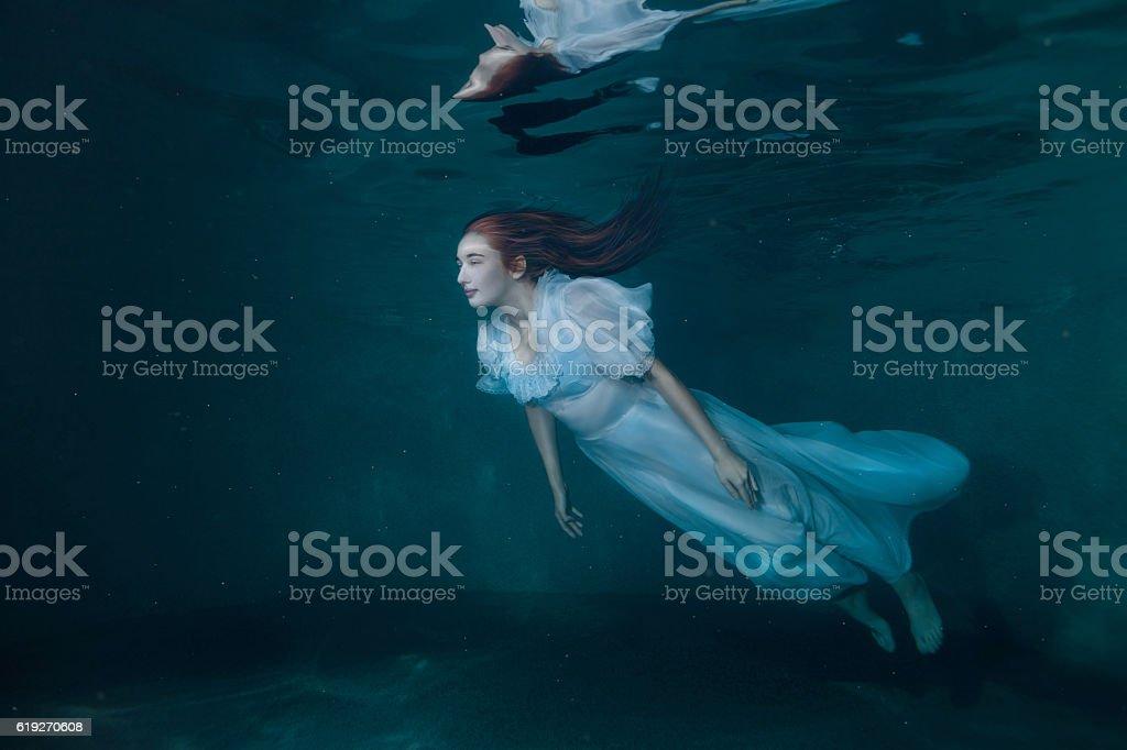 Fairy woman in white dress underwater. stock photo