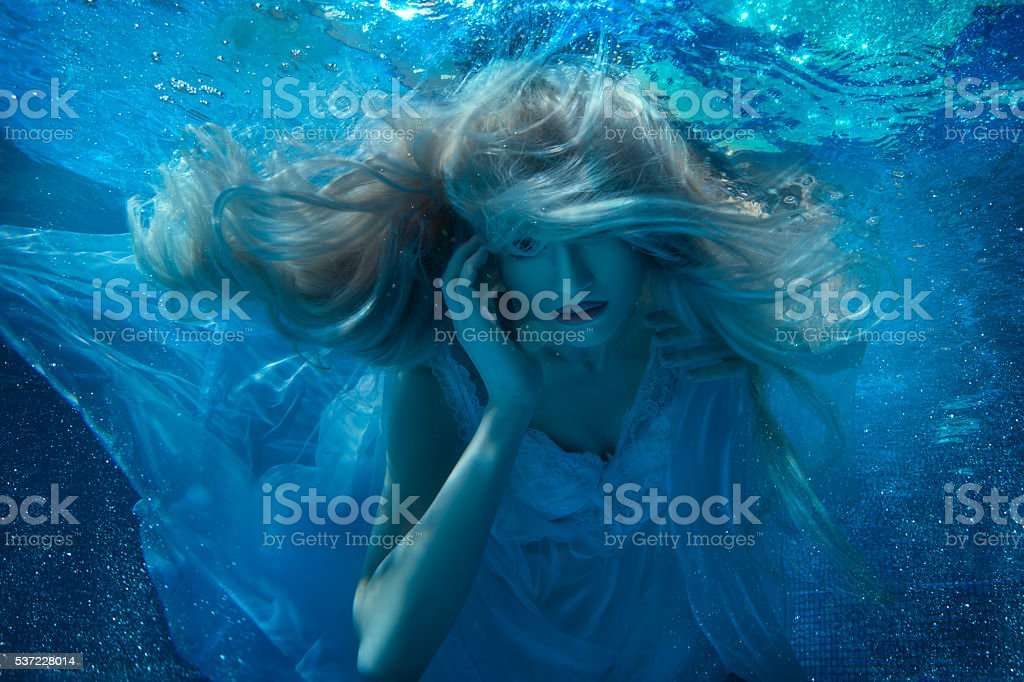 Fairy woman under water in a white dress. stock photo
