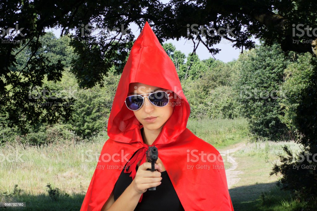 Fairytale armed hold-up by Little Red Riding Hood gangster stock photo