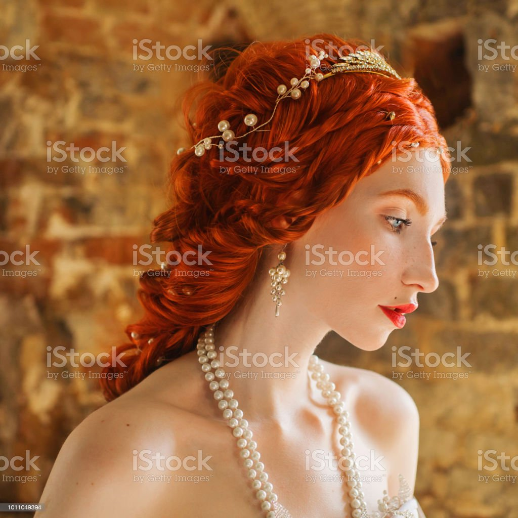 9df26055cc0 Renaissance redhead princess with hairstyle in castle. Fabulous rococo queen  in white dress against the backdrop of old stone wall. Doll in the corset.