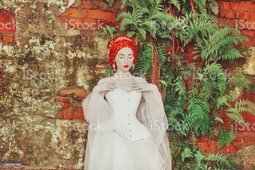 338848b990c Renaissance redhead princess with hairstyle in castle. Fabulous rococo  duchess in white dress against the backdrop of old fern wall. Duchess in  corset.