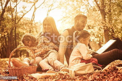 Fairytale in nature.  Happy family having picnic. Father teaching daughter to read.
