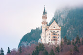 Neuschwanstein, Bavaria, Germany - March 21, 2017: World-famous tourist attraction in the Bavarian Alps, fairytale Neuschwanstein or New Swanstone Castle, the 19th century Romanesque Revival palace in the foggy day, Hohenschwangau, Bavaria, Germany