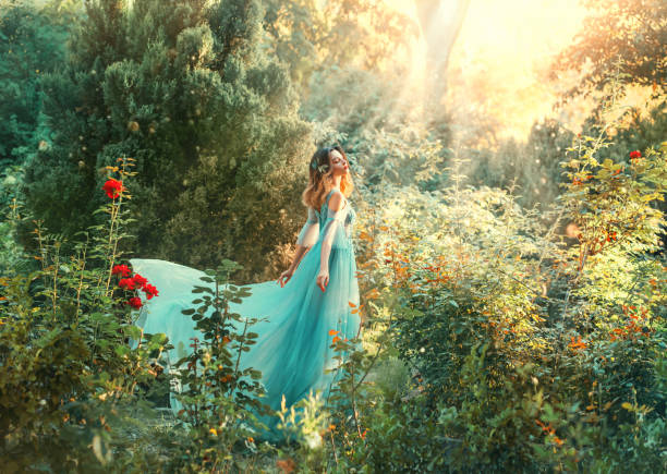Fairytale nymph enjoy bright sun in green forest. Hairstyle decorated blue flowers flowing hair. Fairy in long blue airy dress train fly wavy. Backdrop natural tree bushes of red roses divine sunbeams Fairytale nymph enjoy bright sun in green forest. Hairstyle decorated blue flowers flowing hair. Fairy in long blue airy dress train fly wavy. Backdrop natural tree bushes of red roses divine sunbeams sun shining through dresses stock pictures, royalty-free photos & images