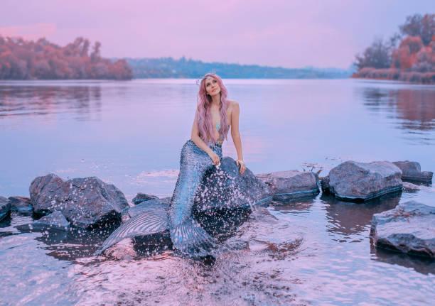 märchenhafte meer königin mit rosa langen haaren, qualle, sitzen auf steinen, verträumt schaut lila himmel, meerjungfrau spritzer, besprüht wasser mit langen, schuppige endstück, pastellfarben, tochter von herr der meere - meerjungfrau kleid stock-fotos und bilder