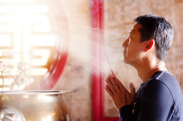 Faith and religious. Man hands holding joss sticks blessing in front of altar table at chinese shrine with sunlight through window,side view. taoism stock pictures, royalty-free photos & images