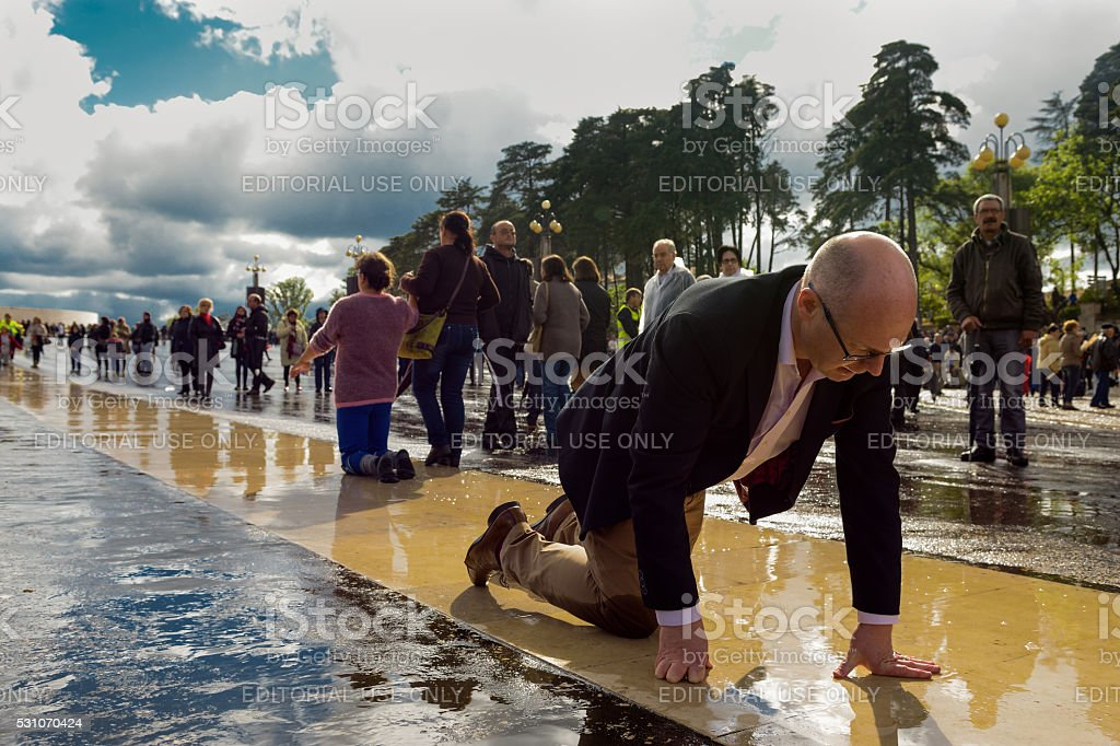 """faith in the shrine of fatima Fatima,Portugal-May 12, 2016: a middle-aged man expresses his faith in the Shrine of Fatima during the celebrations of the 99th anniversary of the """"Apariçoes"""". 2016 Stock Photo"""
