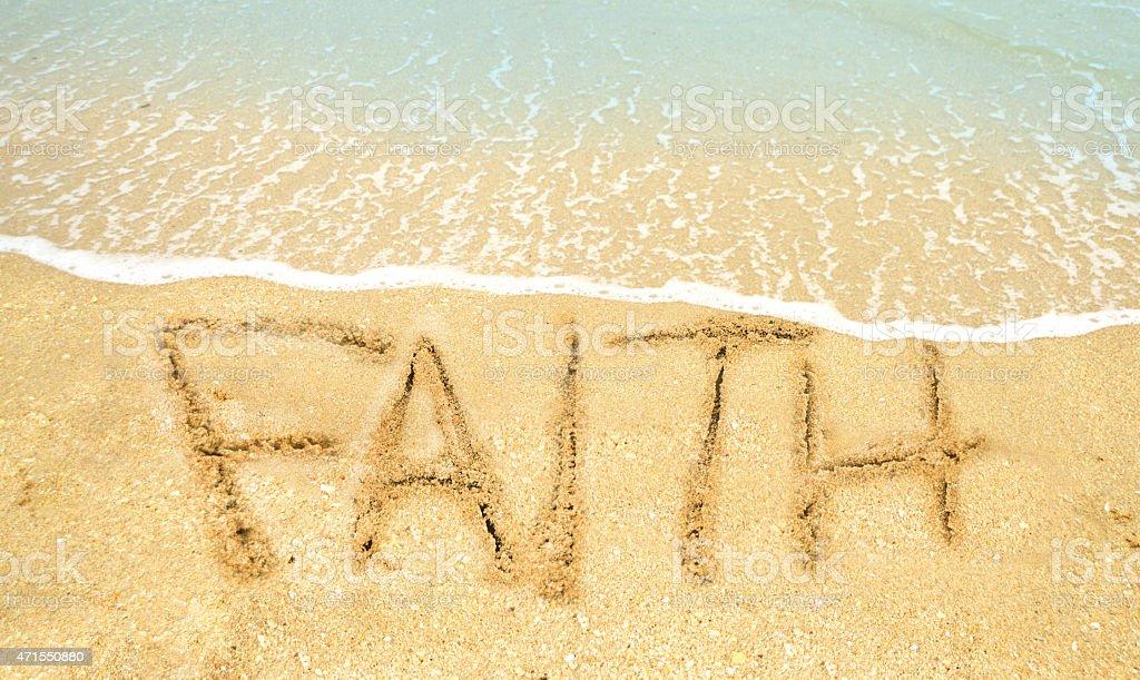 Faith written in sand stock photo