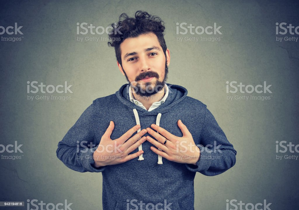 Faithful man keeps hands on chest near heart, shows kindness expresses sincere emotions stock photo