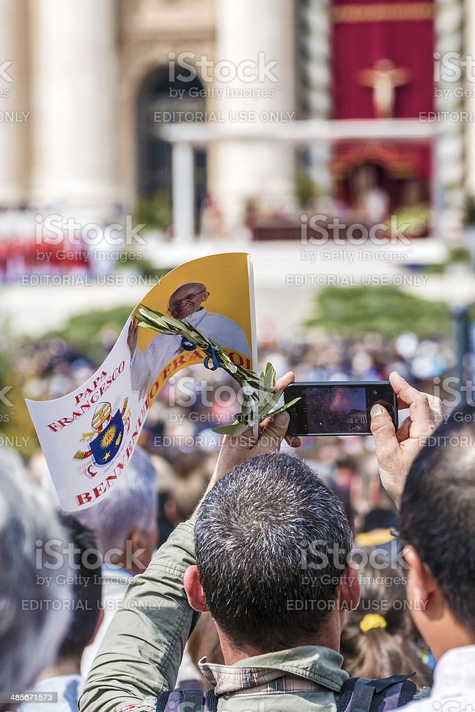 faithful with flag of Pope francis and an olive branch stock photo
