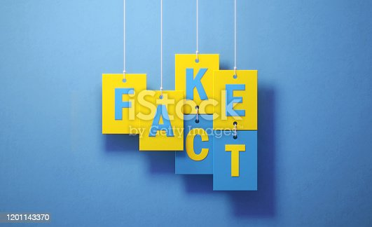 Fake and fact writes over yellow square shapes hanging over blue background, Horizontal composition. Fake news concept.