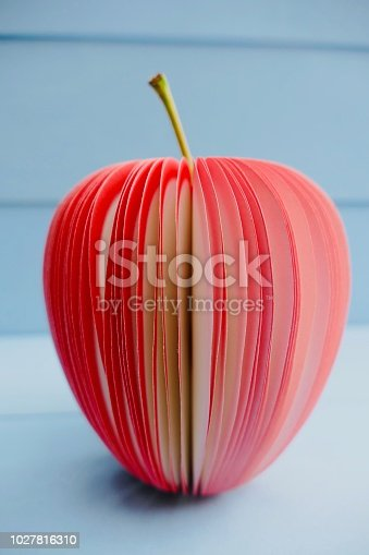 Fake apple made of adhesive notes on blue background