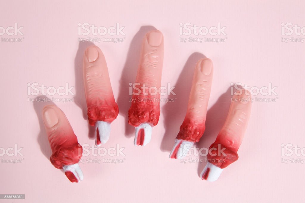 fake bloodied plastic fingers pink background stock photo