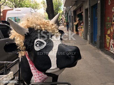 Buenos Aires, Argentina - October 3, 2018: Funny fake cow in the street  next to butcher's shop for advertising purposes. Cow meat is one of the main sources of food here and shops offering it are found all over the city