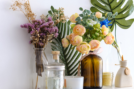 Fake flowers in vases on white wall background