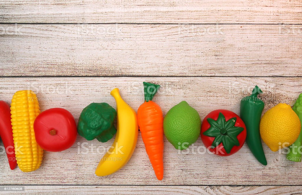 Fake Fruits and Vegetables on a Wooden Table stock photo