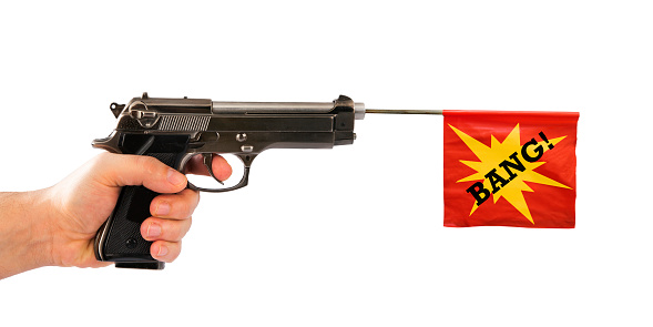 Male hand holding a fake pistol with red flag isolated on white background.