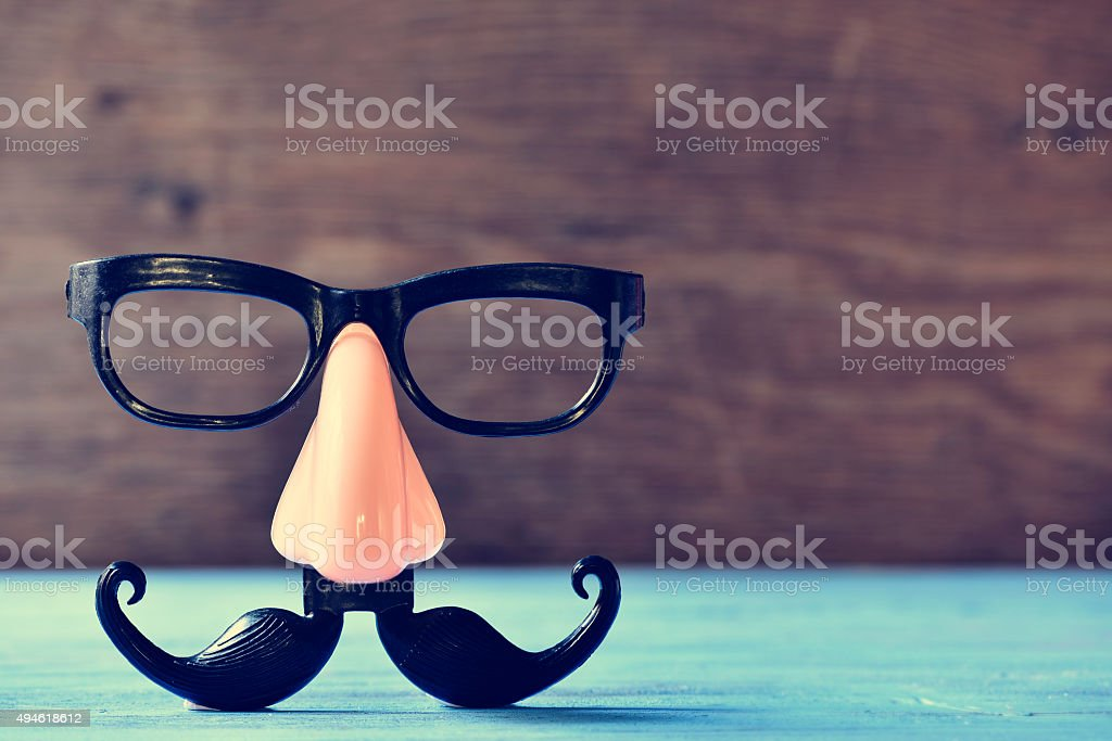fake mustache, nose and eyeglasses on a blue surface stock photo
