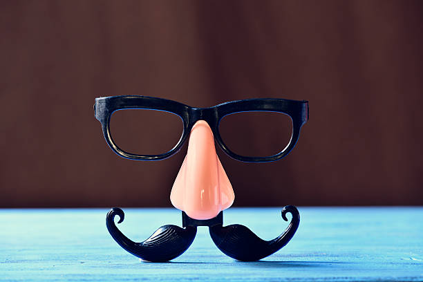 fake mustache, nose and eyeglasses on a blue surface - mask disguise stock photos and pictures