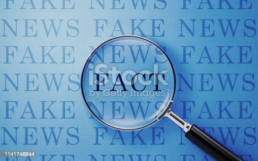 Magnifier and fake/fact news text on blue background. Horizontal composition with copy space.
