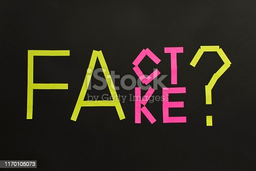 Fake News concept. The inscription FACT and FAKE on a black background