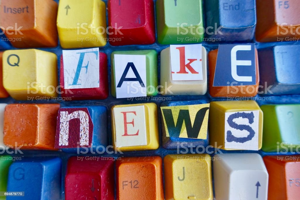 Fake news letters on colorful keys stock photo