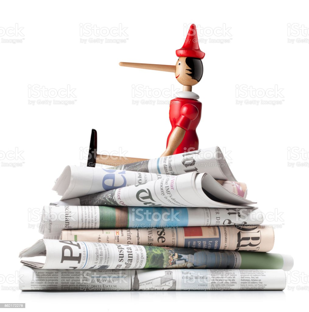 Fake news. Pinocchio on a stack of international newspapers. stock photo