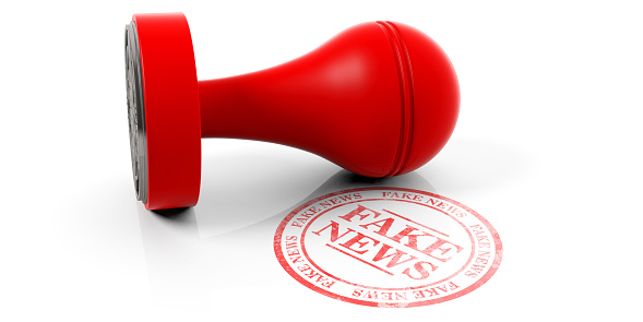 Fake news red round stamp and wooden stamper isolated on white background. 3d illustration
