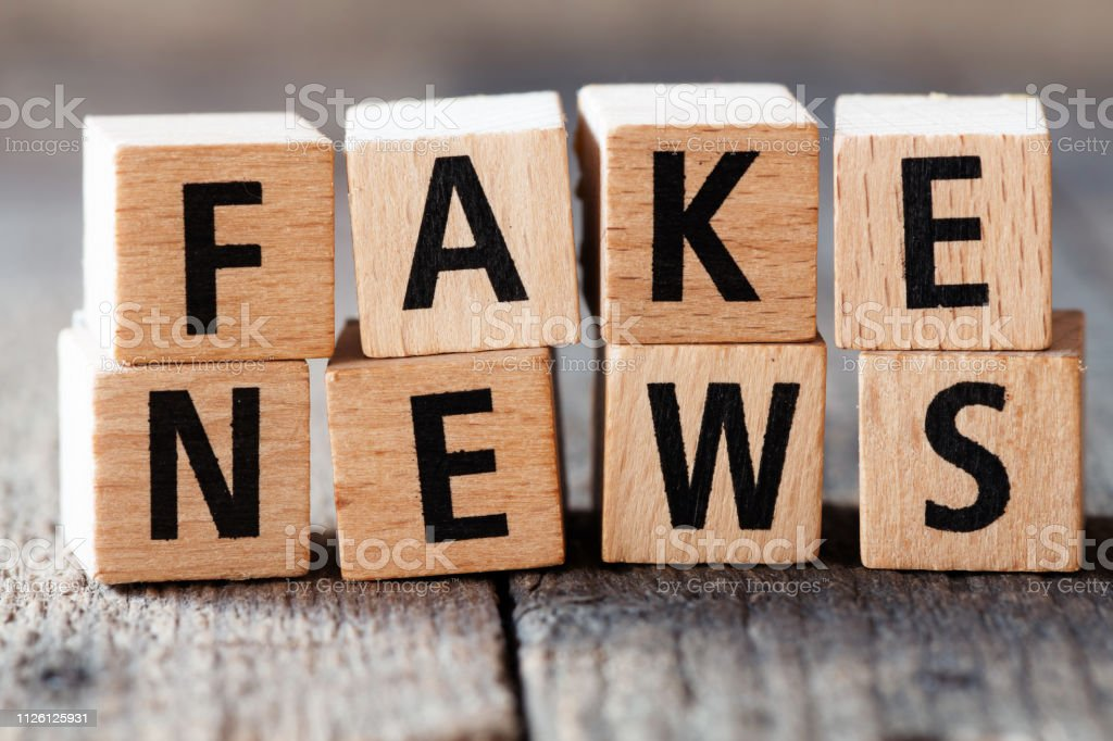 Fake news. Top view of wooden cubes with words fake news on newspapers on wooden background. stock photo