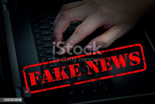 istock Fake news with male hand on keyboard in dark room background. 1055303838