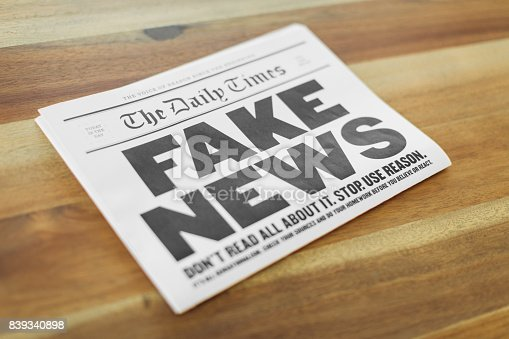 A newspaper publication with the headline Fake News sits folding on a kitchen table. Is the media presenting all the sides of the news story?