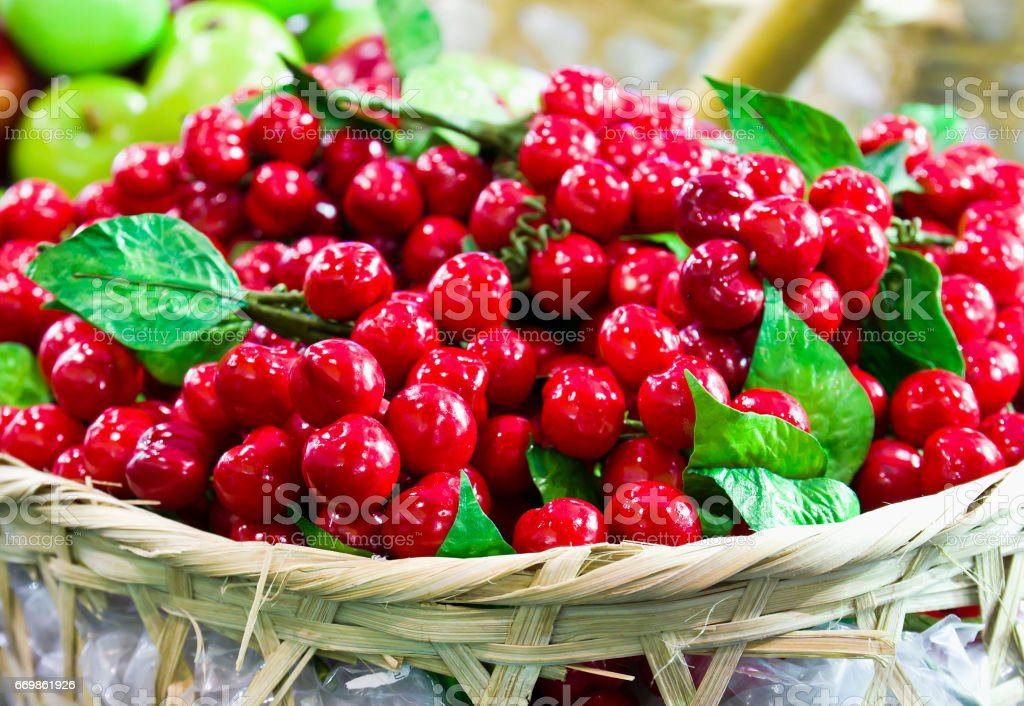 Fake red Cheries on basket stock photo