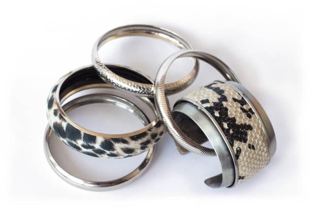 Falsa piel de serpiente y pulseras de plata, aisladas sobre fondo blanco - foto de stock