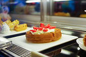 Fake strawberry cream waffle props model displayed on white plate in cafe refrigerator