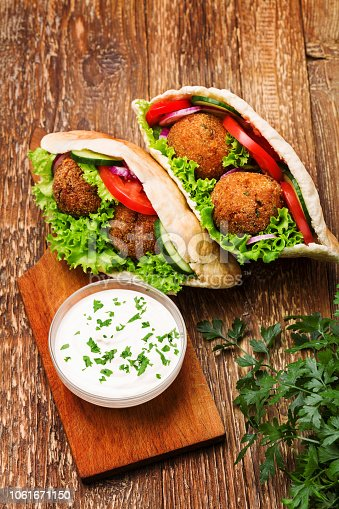 Falafel and fresh vegetables in pita bread on wooden table