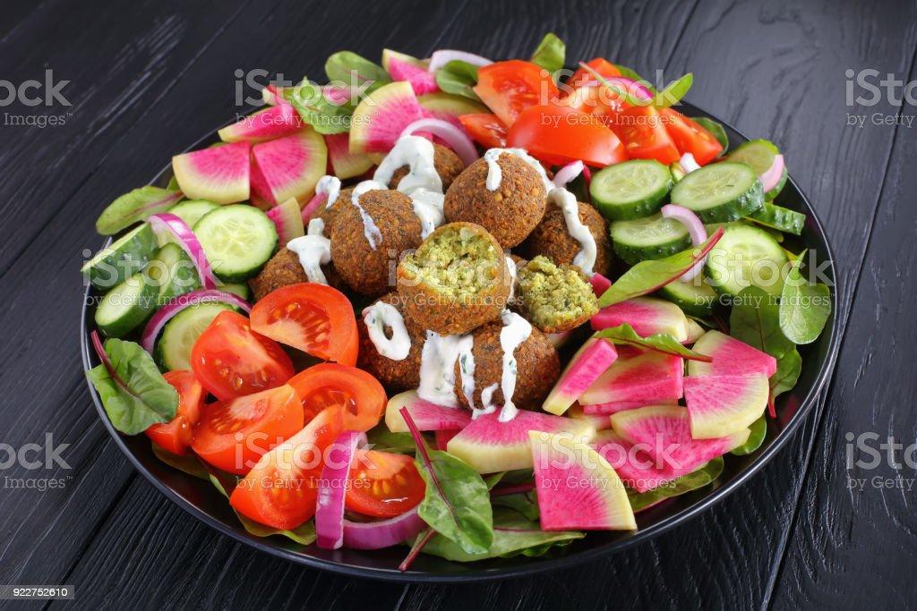 falafel balls on black plate with salad stock photo