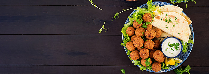 istock Falafel, hummus and pita. Middle eastern or arabic dishes on a dark background. Halal food. Top view. Banner 1139182795