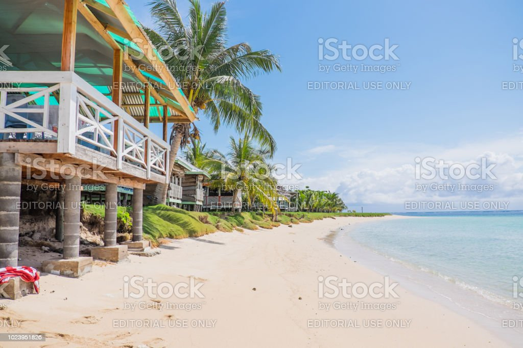 Fale tourist accommodation next to sand and blue sea stock photo