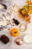 istock Fall and winter beauty and fashion flatlay in warm colors on white marble and wooden table. Little pumpkin, body oil, jewelry, loaf cake, cozy wool skarf, candles and orange leaves. 853308278