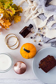 istock Fall and winter beauty and fashion flatlay on white marble table. Blogging concept. Little pumpkin, body oil, jewelry, loaf cake, cozy wool skarf, candles and orange leaves. 853308268