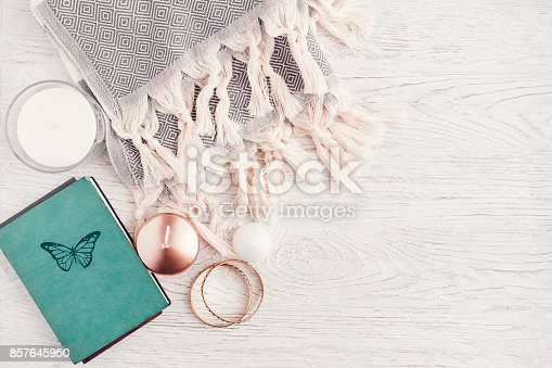 Fall and winter woman fashion still life on white wooden table. Cozy wool scarf, notebook, rose gold candle, jewelry. Copy space, blogging concept